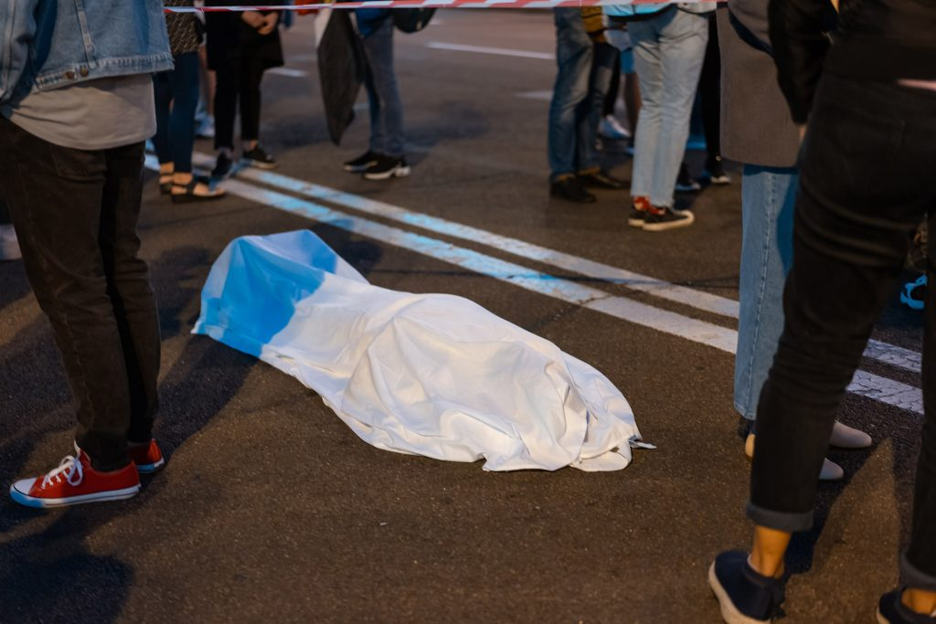 Human body covered by a sheet lying on the street. Crowd around